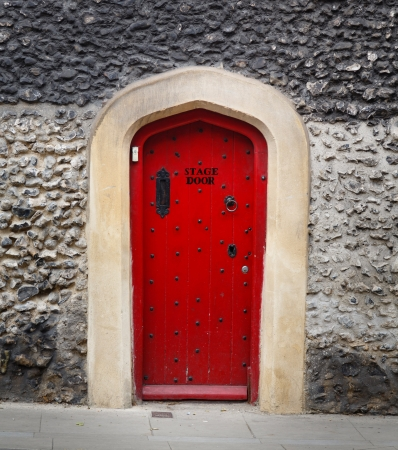 Ancient wooden door in a stone wall, painted red and with the words Stage Door Stock Photo - 17366497