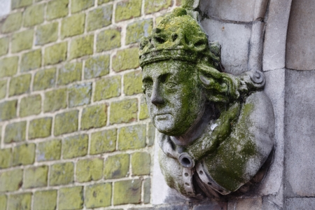 heads old building facade: Detail of a historic building in Winchester with a carved stone figure head on the wall
