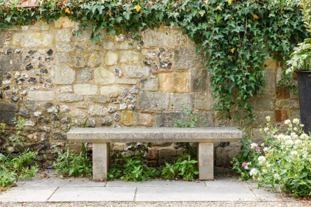 Bench in a formal garden with an old stone wall photo