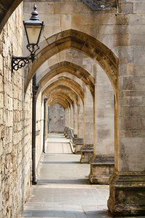 Passage way beside an ancient stone cathedral wall, Winchester, Hampshire, UK