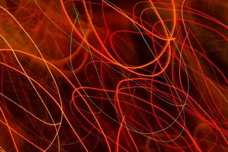 Red and orange light trails against a black background Stock Photo - 18099144