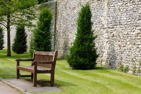 Wooden bench in a formal garden next to an ancient Roman wall in Winchester, UK photo