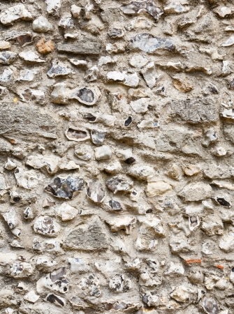 solidity: Detail of the patterns and texture on an old flint and stone wall