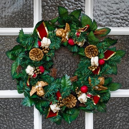 coronas de navidad: Cierre de festivo corona de Navidad que cuelga en una puerta Foto de archivo