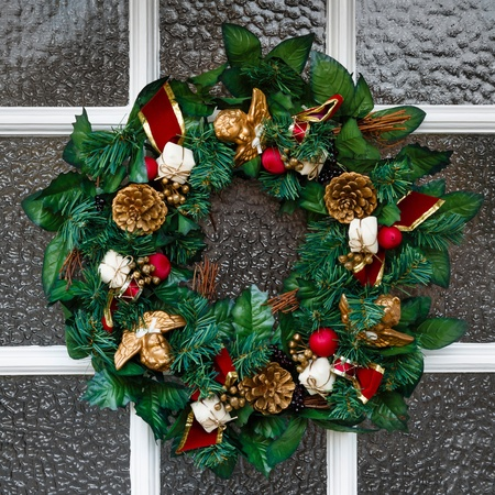 Close up of festive Christmas wreath hanging on a door photo