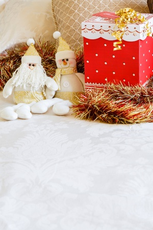 Christmas gift on cream bed linen with copyspace photo