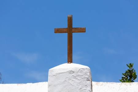 protestant: Wooden cross on a white church against a blue sky in Spain