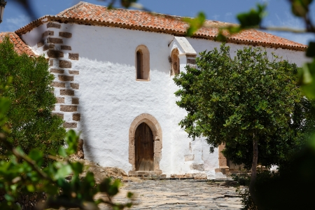 Typical home in Spain with whitewashed walls and terracota roof tiles photo