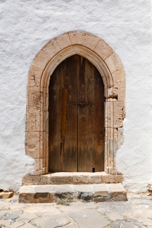 Ancient wooden arched door with stone archway and stucco white wall photo