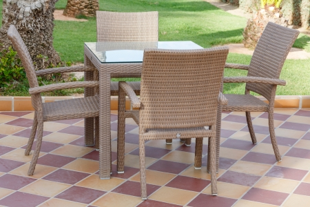 Cane outdoor patio furniture with glass table and chairs on tiled floor