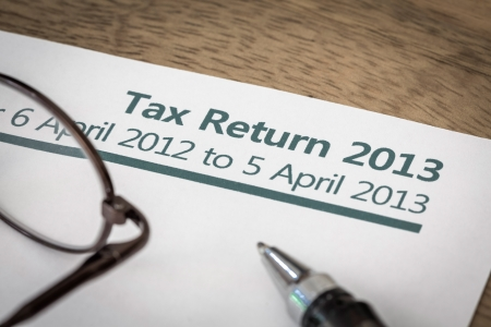 UK Income tax return form for 2013 on a desk with pen and glasses photo