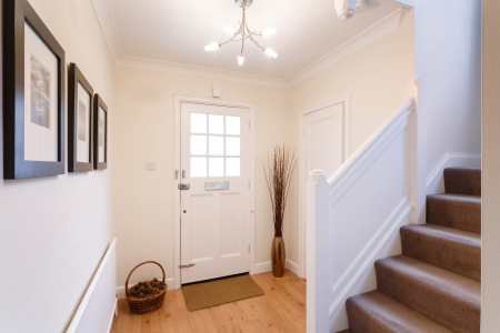 Home interior showing hallway and carpeted stairs photo