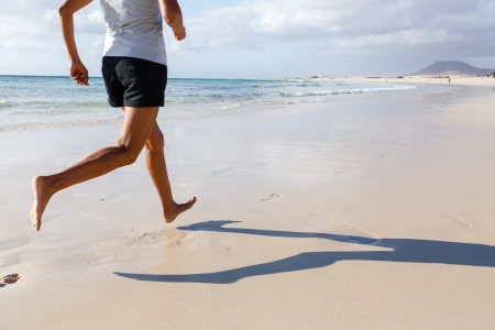 Fit Asian runner jogging on beach barefoot photo