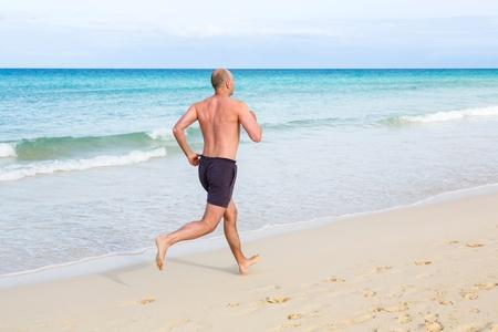 hombre calvo: Hombre de mediana edad para correr en verano en una playa
