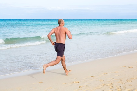 bald: Middle aged man jogging in summer on a beach