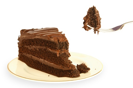 Slice of rich chocolate cake with a mouthful being lifted on a fork photo