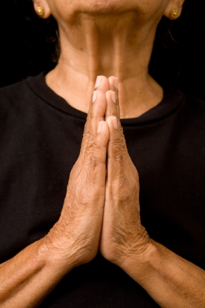 repentance: An old asian woman holds her hands in prayer