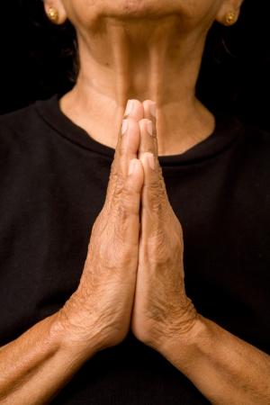 arrepentimiento: Una vieja mujer asiática tiene sus manos en oración