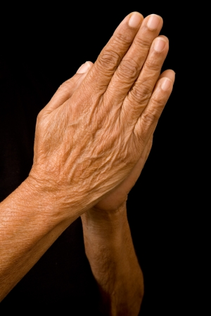 An old asian woman holds her hands in prayer photo