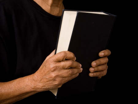 hardback: An old woman holds a bible in prayer
