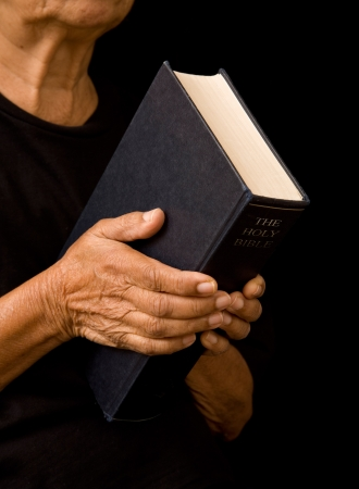 the sermon: An old woman holds a bible in prayer