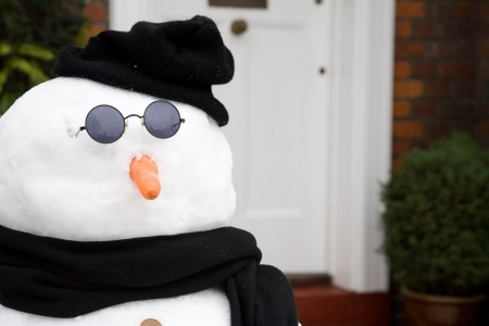 Snowman outside the front door of a traditional house Stock Photo - 21616462