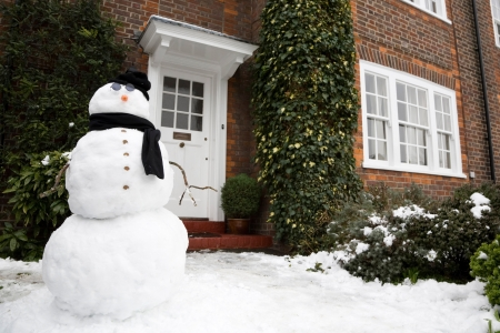 Snowman at the front door of a house in winter Stock Photo