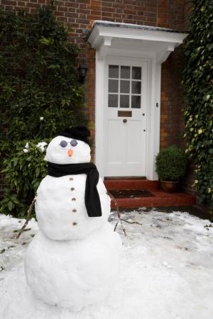 Sneeuwman bij de voordeur van een huis in de winter Stockfoto