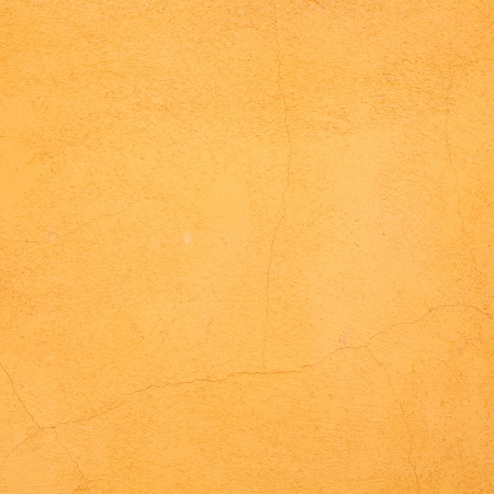Orange painted wall with stucco render texture and cracks, ideal for a vintage background photo