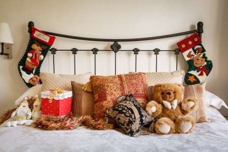 bedstead: Cozy Christmas bedroom scene with Christmas stockings on bedstead