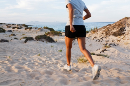 Female Indian jogger jogging on a beach photo