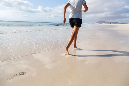 Asian Indian woman running on beach barefoot photo