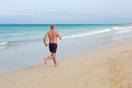 beaches of spain: Middle aged man jogging in summer on a beach