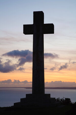 silhoutted: Christian cross silhoutted against a sunset over ocean Stock Photo