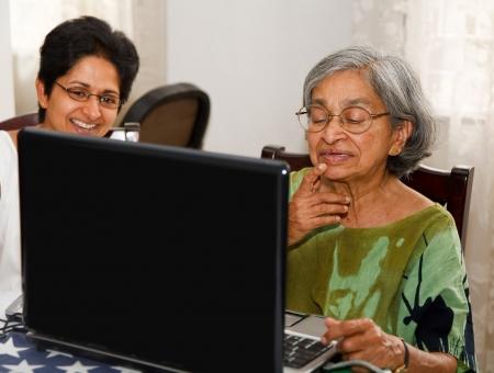 net surfing: Madre indiana e figlia navigare in internet su un computer portatile