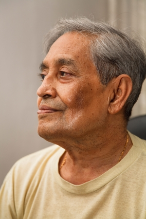 Portrait of old Indian Asian man seated in casual dress photo