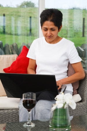conservatories: Young Indian Asian woman uses a laptop in a stylish home
