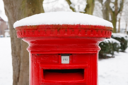 Traditional English red postbox covered with snow Stock Photo