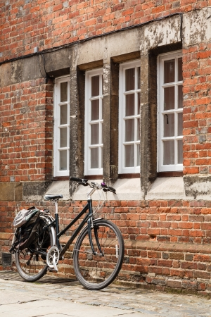 Retro bicycle leaning against an old brick wall photo