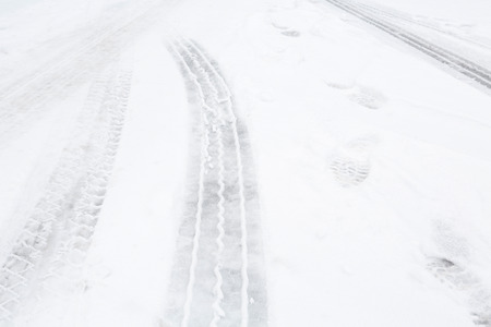 Closeup of tire tracks on a street with snow photo