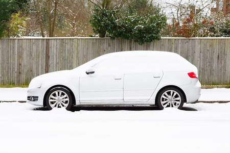 Parked European car covered in snow in England Stock Photo