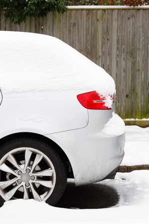Side of car covered in snow parked on a British road in winter photo