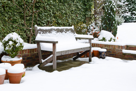 Snow covered garden bench on a patio in winter