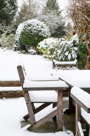 Snow covered patio furniture in a garden in winter Stock Photo