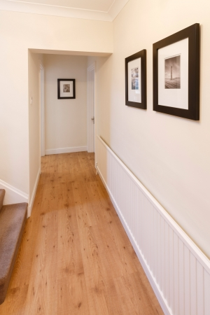 showhome: Hallway in a home with wooden floor and pictures on the wall