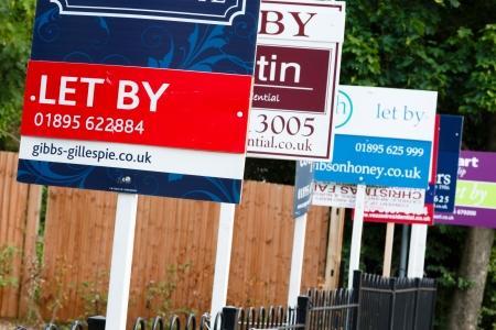 let on: Londres, Reino Unido, 2013 Agencia inmobiliaria dej� por signos anuncian propiedad en un suburbio de Londres Editorial