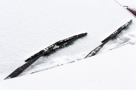 Closeup of a car windshield and wipers covered with snow