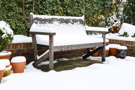 Garden bench in winter covered with snow photo