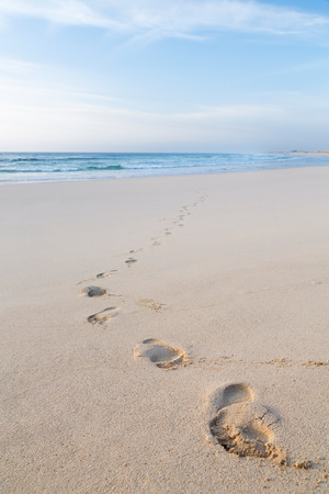 Footprints of feet on a beach walking away from the sea photo