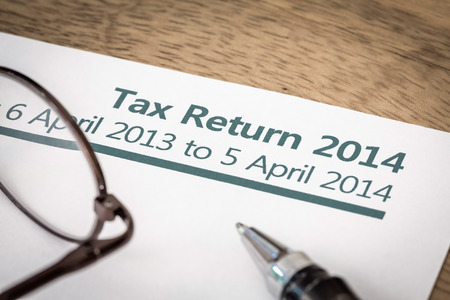 UK Income tax return form for 2014 on a desk with pen and glasses